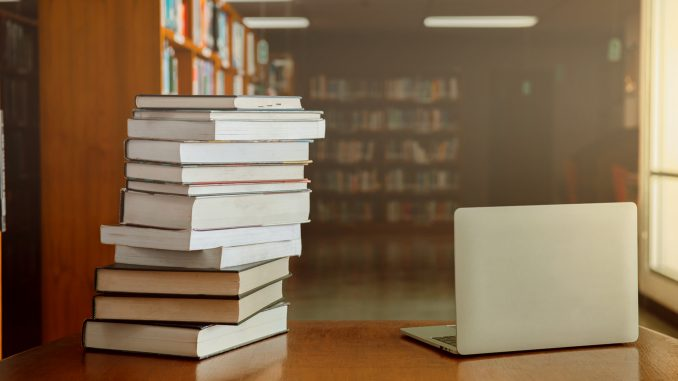 Stack of old books and laptop computer on desk in library background.