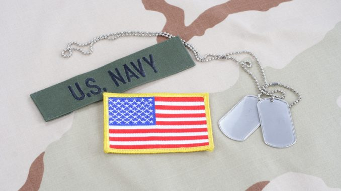 US NAVY branch tape with dog tags and flag patch on desert camouflage uniform background