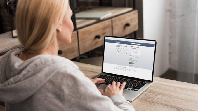 back view of woman using laptop with facebook social network website on screen