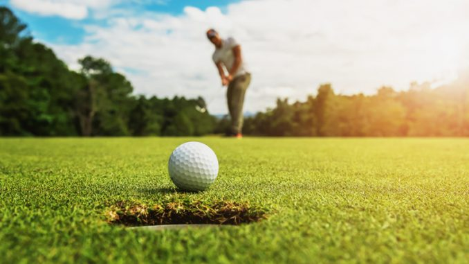 golf player putting golf ball into hole with sunshine
