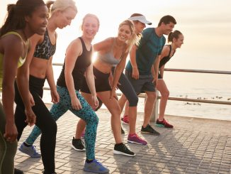 Running club members training together in morning under a bridge.