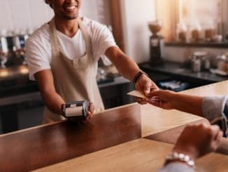 Customer paying through credit card at coffee shop.