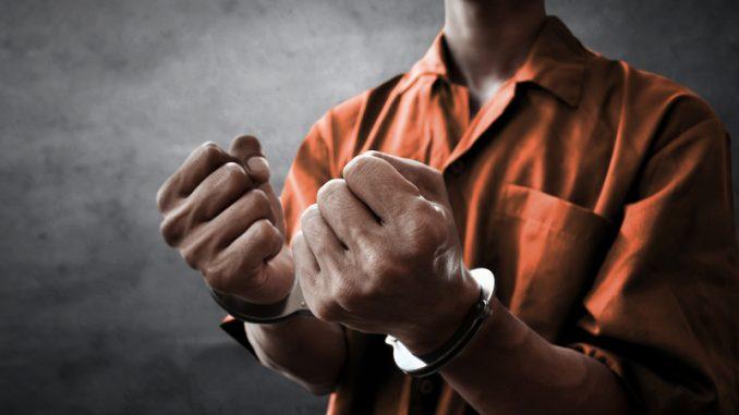 Arrested man in handcuffs in prison