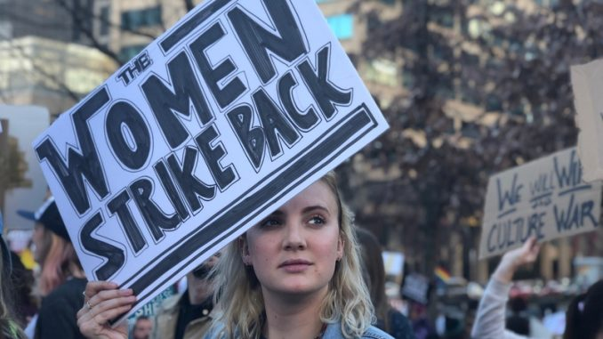 Blonde Woman holding War style protest sign representing the Me Too movement