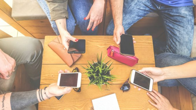 Top view of a group of hipster friends sitting in a bar cafe using mobile smart phone - New young generation trend