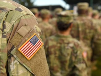 American Soldiers and Flag of USA on soldiers arm. US Army. Veteran Day.