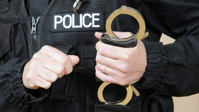 Uniformed police officer holding handcuffs