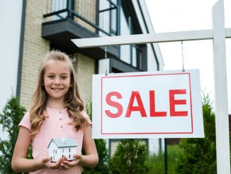 Cheerful kid holding carton house model near board with sale letters