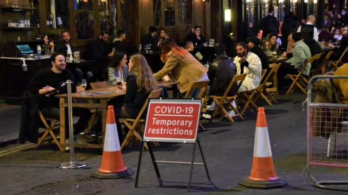 Outdoor street seating at bars and restaurants with COVID-19 Temporary Restrictions sign